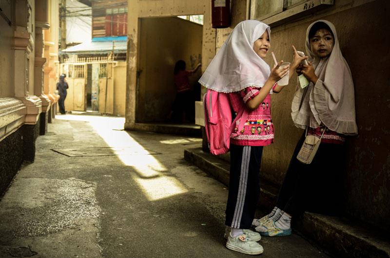 เด็กผู้หญิงสองคนกำลังยืนคุยกันหลังเลิกเรียน ระหว่างรอผู้ปกครองมารับที่มัสยิด