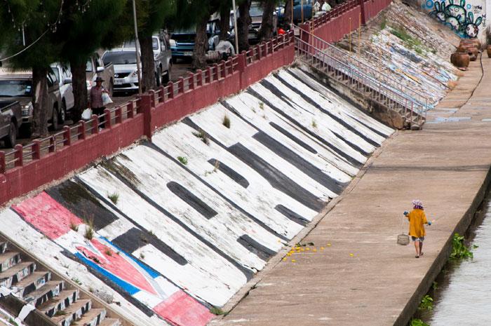 """ลวดลายกราฟฟิตี้ที่ถูกพ่นลงตลอดแนวเขื่อนแม่น้ำ ผลงานของกลุ่มกราฟฟิตี้เมืองราชบุรีที่ใช้ชื่อกลุ่มว่า """"JARTOWN"""" ช่วยสร้างสีสันให้กับเมืองราชบุรี และกลายเป็นที่ที่นักท่องเที่ยวชอบมาถ่ายภาพกัน"""