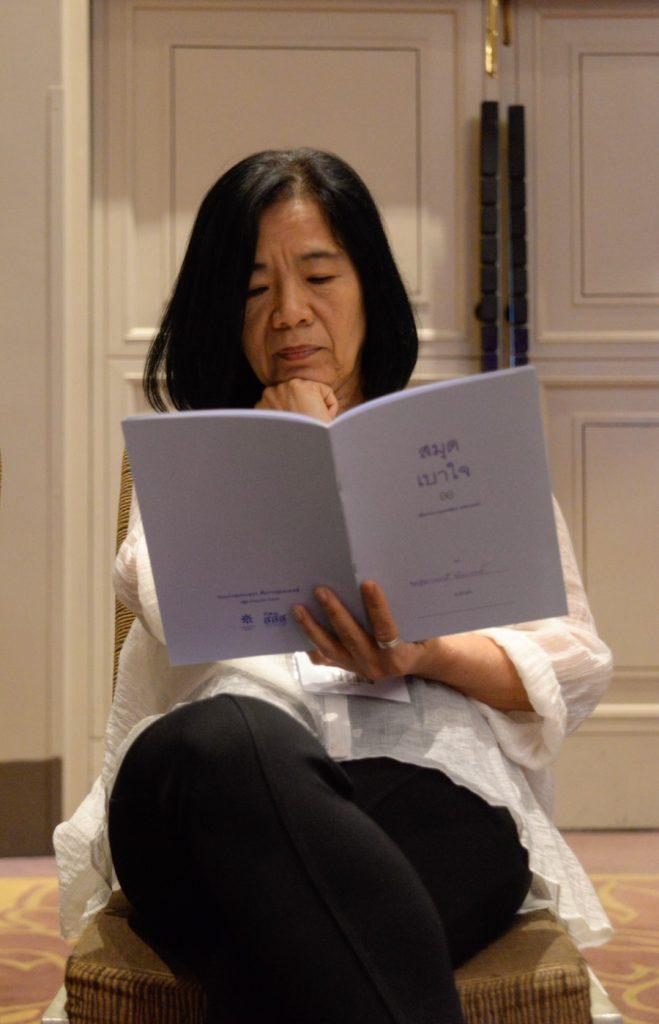 ผู้เข้าร่วมกิจกรรมอ่านสมุดเบาใจอย่างตั้งอกตั้งใจ เพื่อเตรียมเขียนเจตนารมณ์ของตัวเองลงในสมุด (ภาพ : อมรกิตติยา สิทธิชัย)