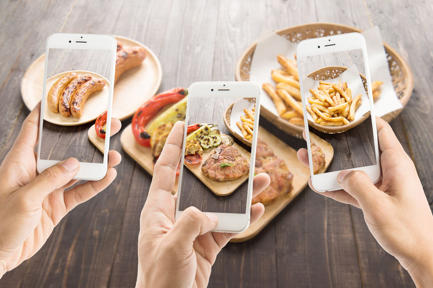 39980334 - friends using smartphones to take photos of sausage and pork chop and french fries.