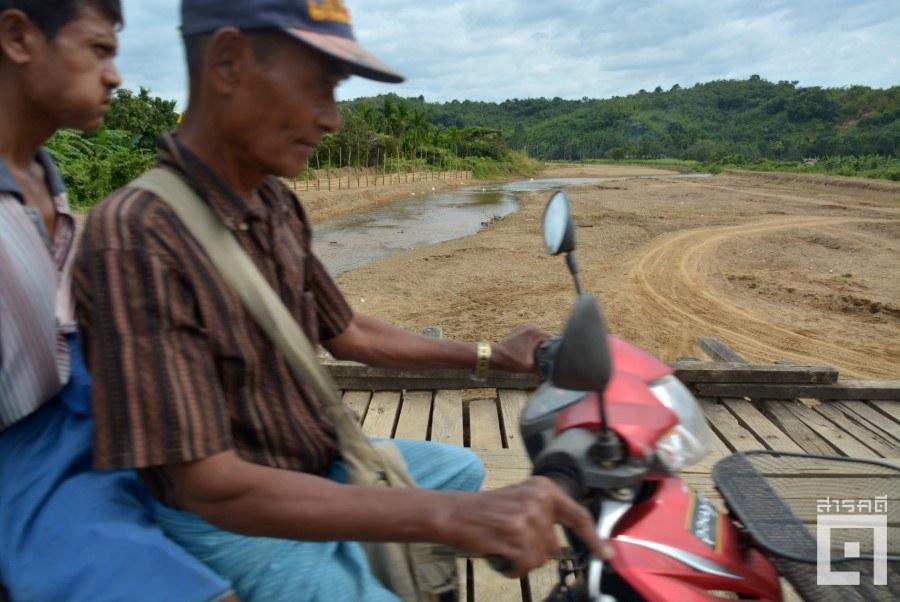 ชาวบ้านขี่มอเตอร์ไซด์ผ่านสะพานข้ามแม่น้ำเมียวพิวที่ตื้นเขินและเปลี่ยนแปลงหลังการทำเหมืองแร่ (ภาพ : ฐิติพันธ์ พัฒนมงคล)