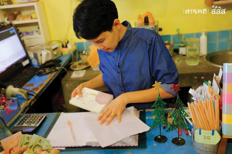 หนังสือเจ้าชายน้อยฉบับภาษาไทยที่ลูกค้าชาวเกาหลีใต้เลือกไปเพื่อเก็บสะสม กำลังถูกใส่ลงไปในห่อกระดาษอย่างประณีต
