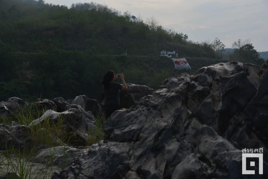 โขดหินบริเวณคอนผีหลง ชุมทางแก่งใหญ่ยาวต่อเนื่องเกือบ ๒ กิโลเมตรกลางลำน้ำโขง เป็นอีกบริเวณที่เคยถูกสำรวจเพื่อหาทางระเบิดแก่ง บนหน้าผาห่างออกไปเป็นป้ายผ้าเขียนข้อความรณรงค์หยุดระเบิดแก่งเมื่อหลายปีก่อน (ภาพ : ฐิติพันธ์ พัฒนมงคล)